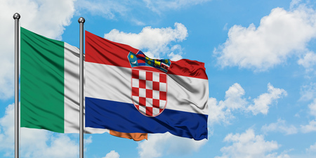 Ireland and Croatia flag waving in the wind against white cloudy blue sky together. Diplomacy concept, international relations. Stock Photo