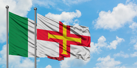 Italy and Guernsey flag waving in the wind against white cloudy blue sky together. Diplomacy concept, international relations. Standard-Bild