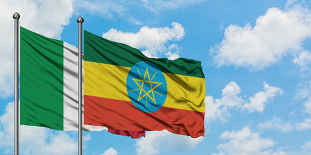 Italy and Ethiopia flag waving in the wind against white cloudy blue sky together. Diplomacy concept, international relations.