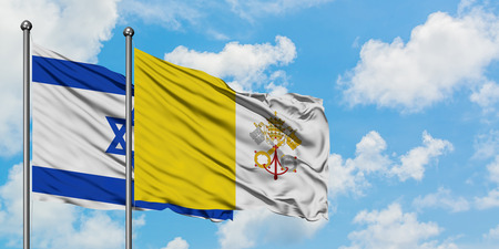 Israel and Vatican City flag waving in the wind against white cloudy blue sky together. Diplomacy concept, international relations.