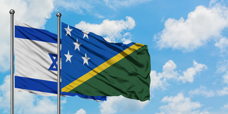 Israel and Solomon Islands flag waving in the wind against white cloudy blue sky together. Diplomacy concept, international relations. Stok Fotoğraf