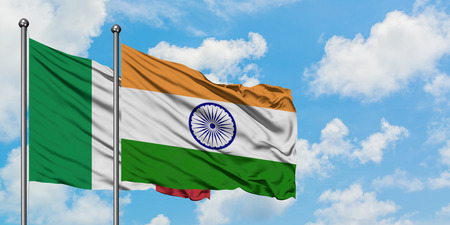 Italy and India flag waving in the wind against white cloudy blue sky together. Diplomacy concept, international relations.