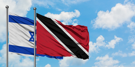 Israel and Trinidad And Tobago flag waving in the wind against white cloudy blue sky together. Diplomacy concept, international relations. Stock Photo
