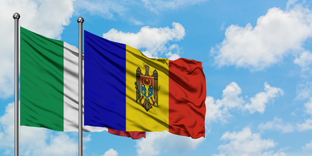 Italy and Moldova flag waving in the wind against white cloudy blue sky together. Diplomacy concept, international relations.