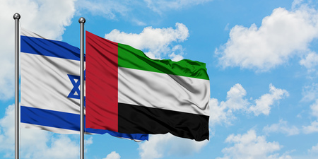 Israel and United Arab Emirates flag waving in the wind against white cloudy blue sky together. Diplomacy concept, international relations. Banco de Imagens