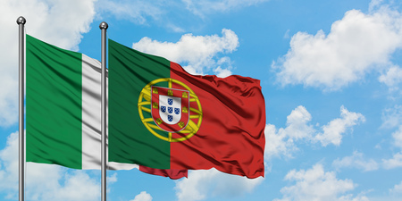 Italy and Portugal flag waving in the wind against white cloudy blue sky together. Diplomacy concept, international relations. Standard-Bild