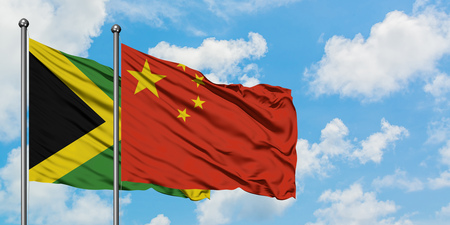 Jamaica and China flag waving in the wind against white cloudy blue sky together. Diplomacy concept, international relations.