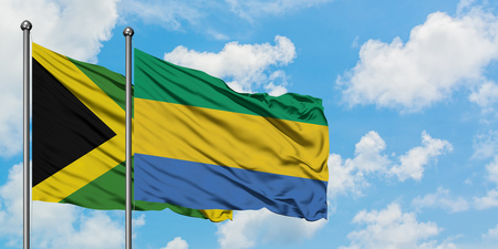 Jamaica and Gabon flag waving in the wind against white cloudy blue sky together. Diplomacy concept, international relations.