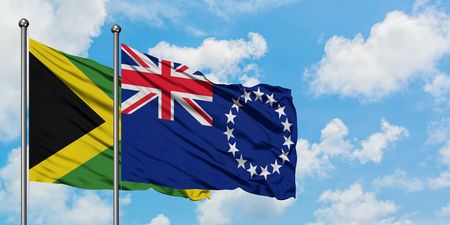 Jamaica and Cook Islands flag waving in the wind against white cloudy blue sky together. Diplomacy concept, international relations. Stock Photo