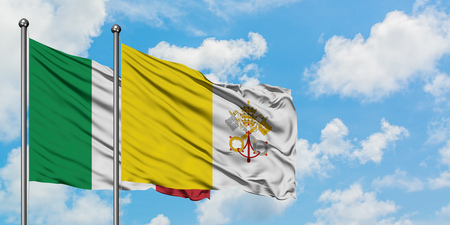 Italy and Vatican City flag waving in the wind against white cloudy blue sky together. Diplomacy concept, international relations.