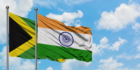 Jamaica and India flag waving in the wind against white cloudy blue sky together. Diplomacy concept, international relations.