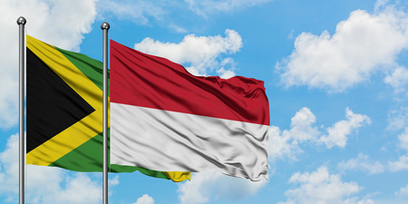 Jamaica and Indonesia flag waving in the wind against white cloudy blue sky together. Diplomacy concept, international relations.