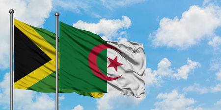 Jamaica and Algeria flag waving in the wind against white cloudy blue sky together. Diplomacy concept, international relations. Stock Photo