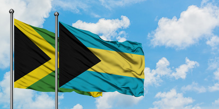 Jamaica and Bahamas flag waving in the wind against white cloudy blue sky together. Diplomacy concept, international relations. Stock Photo - 123803574