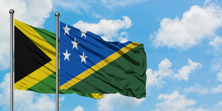 Jamaica and Solomon Islands flag waving in the wind against white cloudy blue sky together. Diplomacy concept, international relations. Stok Fotoğraf