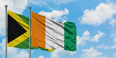 Jamaica and Cote DIvoire flag waving in the wind against white cloudy blue sky together. Diplomacy concept, international relations.