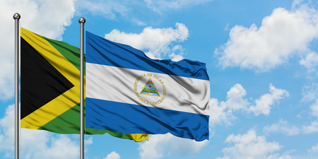 Jamaica and Nicaragua flag waving in the wind against white cloudy blue sky together. Diplomacy concept, international relations. Stock Photo