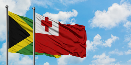 Jamaica and Tonga flag waving in the wind against white cloudy blue sky together. Diplomacy concept, international relations. Stock Photo