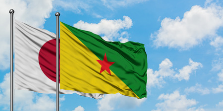 Japan and French Guiana flag waving in the wind against white cloudy blue sky together. Diplomacy concept, international relations. Stock Photo