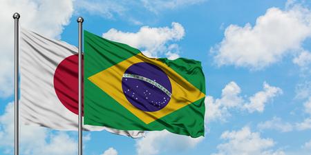 Bandera de Japón y Brasil ondeando en el viento contra el cielo azul nublado blanco juntos. Concepto de diplomacia, relaciones internacionales.