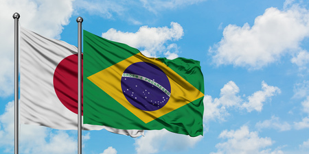 Japan and Brazil flag waving in the wind against white cloudy blue sky together. Diplomacy concept, international relations. Banco de Imagens