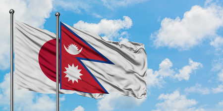 Japan and Nepal flag waving in the wind against white cloudy blue sky together. Diplomacy concept, international relations.