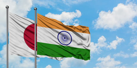 Japan and India flag waving in the wind against white cloudy blue sky together. Diplomacy concept, international relations.