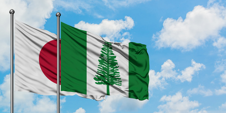 Japan and Norfolk Island flag waving in the wind against white cloudy blue sky together. Diplomacy concept, international relations.