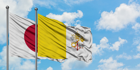 Japan and Vatican City flag waving in the wind against white cloudy blue sky together. Diplomacy concept, international relations.