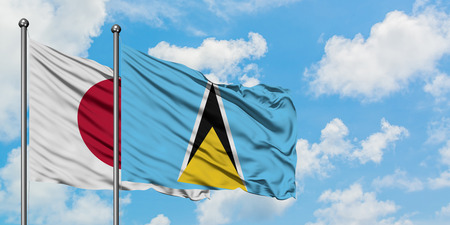 Japan and Saint Lucia flag waving in the wind against white cloudy blue sky together. Diplomacy concept, international relations.
