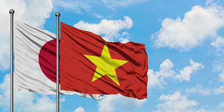 Japan and Vietnam flag waving in the wind against white cloudy blue sky together. Diplomacy concept, international relations.