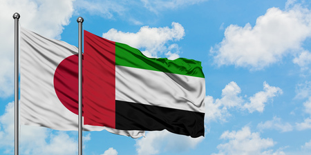 Japan and United Arab Emirates flag waving in the wind against white cloudy blue sky together. Diplomacy concept, international relations.