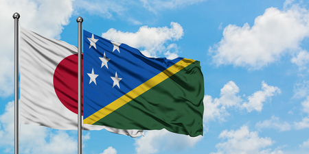 Japan and Solomon Islands flag waving in the wind against white cloudy blue sky together. Diplomacy concept, international relations.