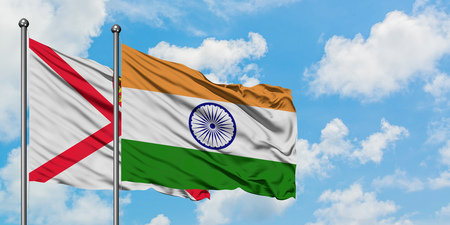 Jersey and India flag waving in the wind against white cloudy blue sky together. Diplomacy concept, international relations. Stock Photo