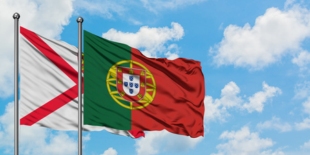 Jersey and Portugal flag waving in the wind against white cloudy blue sky together. Diplomacy concept, international relations.