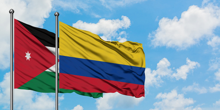 Jordan and Colombia flag waving in the wind against white cloudy blue sky together. Diplomacy concept, international relations.
