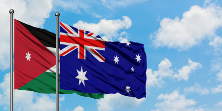 Jordan and Australia flag waving in the wind against white cloudy blue sky together. Diplomacy concept, international relations.