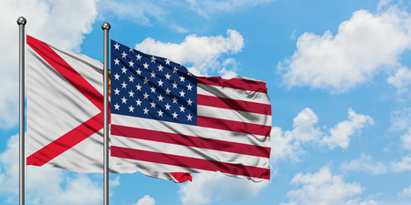Jersey and United States flag waving in the wind against white cloudy blue sky together. Diplomacy concept, international relations.