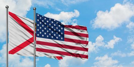 Jersey y la bandera de Estados Unidos ondeando en el viento contra el cielo azul nublado blanco juntos. Concepto de diplomacia, relaciones internacionales.
