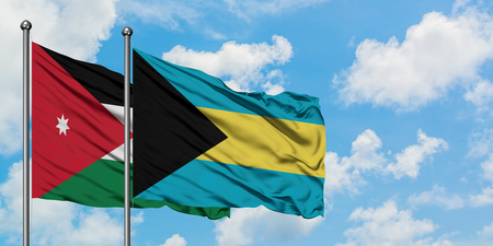 Jordan and Bahamas flag waving in the wind against white cloudy blue sky together. Diplomacy concept, international relations. Stock Photo - 123800570