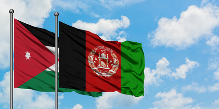Jordan and Afghanistan flag waving in the wind against white cloudy blue sky together. Diplomacy concept, international relations.