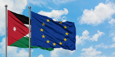 Jordan and European Union flag waving in the wind against white cloudy blue sky together. Diplomacy concept, international relations.