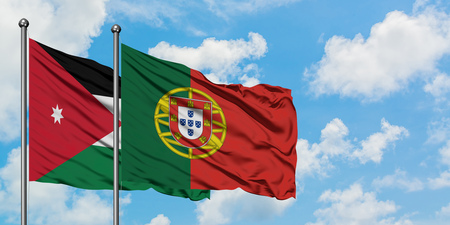 Jordan and Portugal flag waving in the wind against white cloudy blue sky together. Diplomacy concept, international relations. Stock Photo