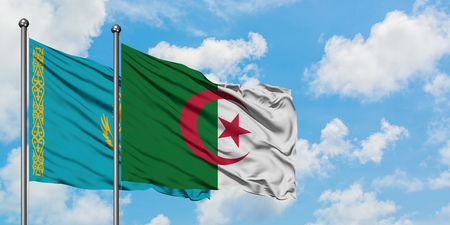 Kazakhstan and Algeria flag waving in the wind against white cloudy blue sky together. Diplomacy concept, international relations.
