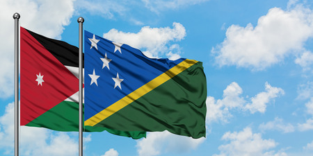 Jordan and Solomon Islands flag waving in the wind against white cloudy blue sky together. Diplomacy concept, international relations. Stok Fotoğraf