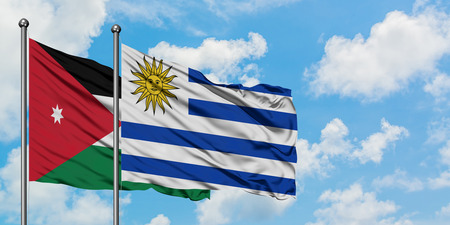 Jordan and Uruguay flag waving in the wind against white cloudy blue sky together. Diplomacy concept, international relations. Banco de Imagens