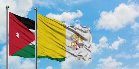 Jordan and Vatican City flag waving in the wind against white cloudy blue sky together. Diplomacy concept, international relations.