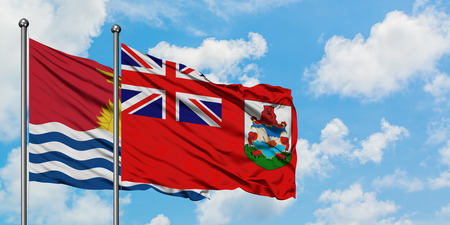 Kiribati and Bermuda flag waving in the wind against white cloudy blue sky together. Diplomacy concept, international relations. Stok Fotoğraf