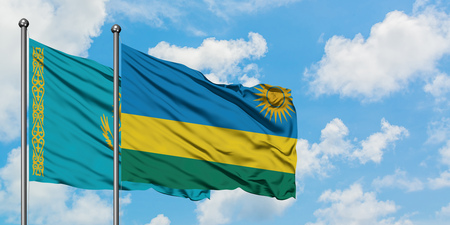 Kazakhstan and Rwanda flag waving in the wind against white cloudy blue sky together. Diplomacy concept, international relations.