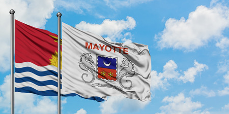 Kiribati and Mayotte flag waving in the wind against white cloudy blue sky together. Diplomacy concept, international relations.